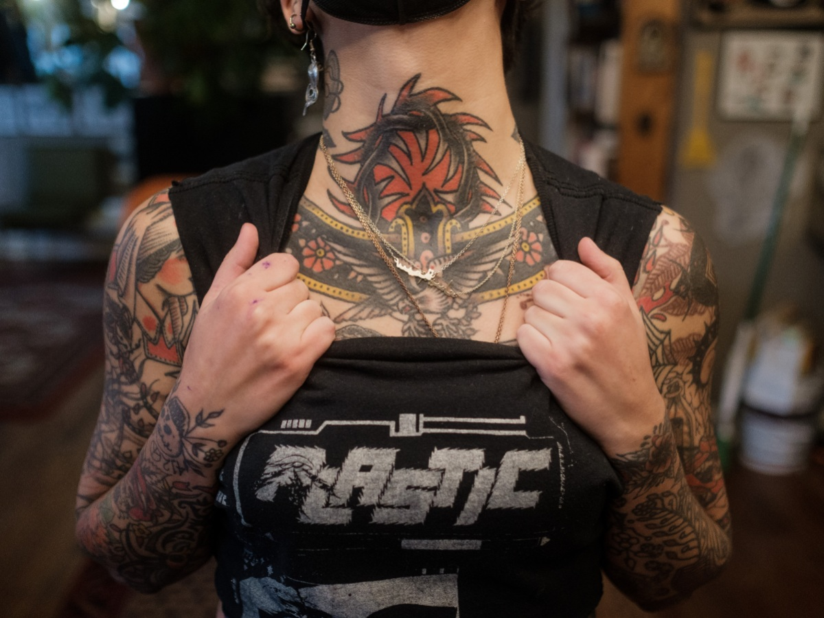 Image shows the heavily tattooed neck of Sema. They are holding their shirt down from the collar and their neck is lifted up.