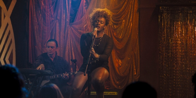 September Mornings: Liniker as Cassandra sings on stage seated wearing a black dress