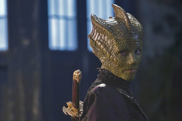 Madame Vastra from Dr Who, a Salurian alien with green lizard-like skin, looking badass with a sword on her back