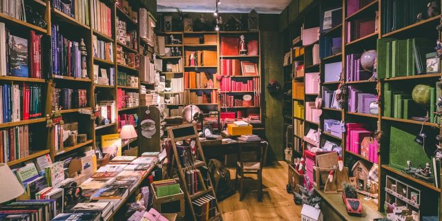 A grainy photo of a corner of a small bookstore in warm lighting, with shelves full of colorful books and a small stepladder and desk