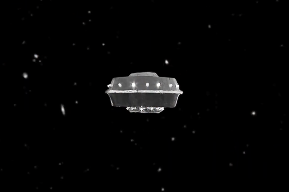A hokey spaceship that looks like it was made out of a tin can hovering against a black starry backdrop