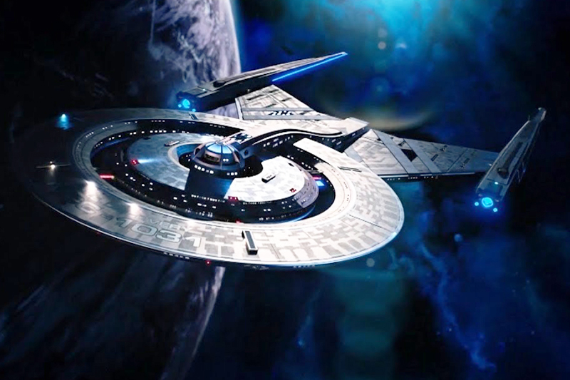 The starship Discovery from Star Trek flaying by a planet against a starry backdrop