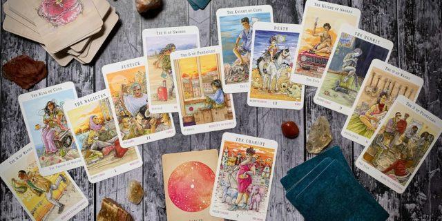 A spread of Next World tarot cards spread over a wooden backdrop