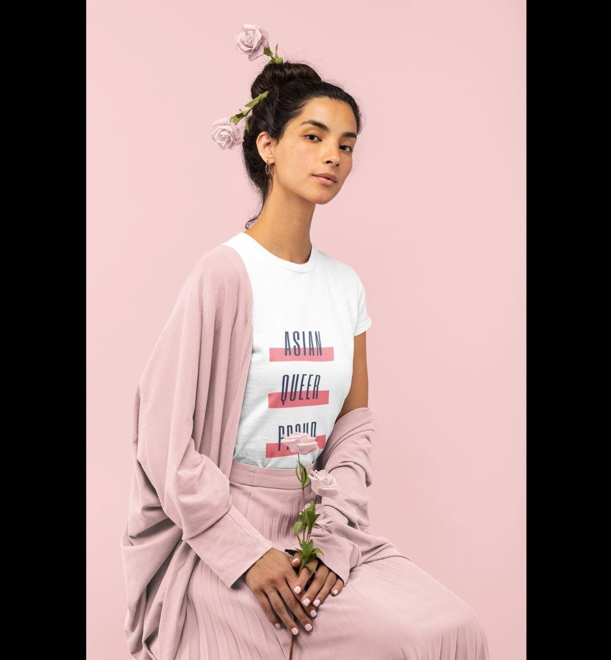 model in a white t-shirt that says ASIAN QUEER PROUD in block letters with red striped styling behind each word. Model is wearing pink pants and a pink cardigan and holding a pink rose.