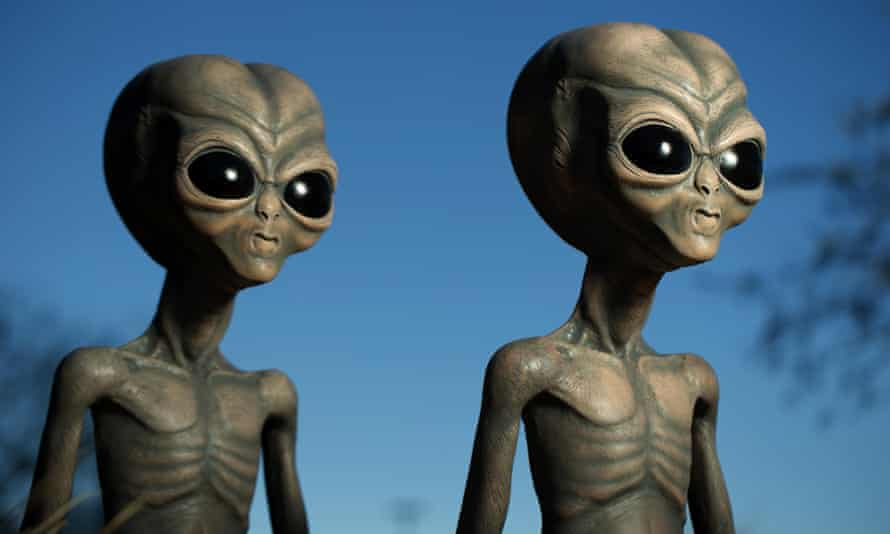 Two classic green-grey skinned aliens with skinny bodies and oversized heads and eyes