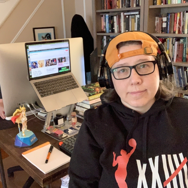 Heather Hogan sits at her desk, laptop open, with a small smile, a figure of she-ra in the backgound, and a glimpse of stacy's hand behind her. also, there is a notebook and pen on the desk and a stack of books. she has headphones, an orange hat, and a WNBA sweatshirt on
