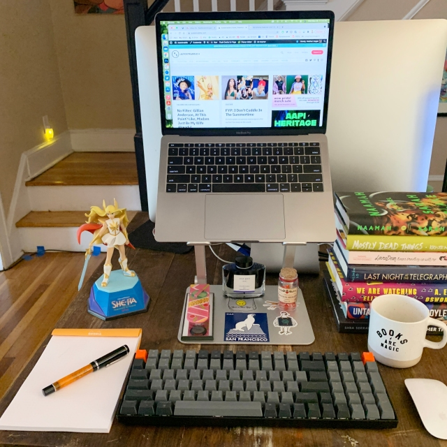 This is Heather Hogan's Desk! It has a laptop with separate keyboard and mouse, notepad and pen, She-Ra figurine, mug, pile of books