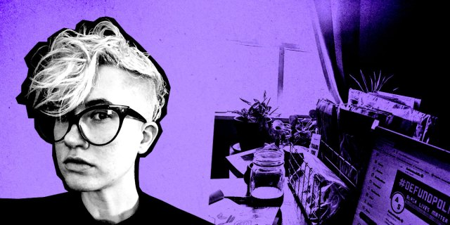 Nicole (a white, non-binary human with bleached hair and shaved sides, large dark glasses) in front of a purple background with their desk behind them.