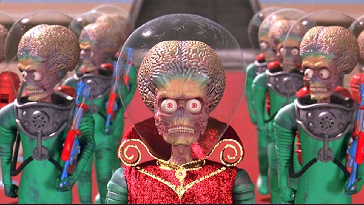 A group of martians from the film Mars Attacks dressed in bright red and green clothes with glass domes over their giant craniums