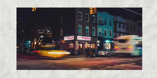 A photo of an NYC intersection at night, with a pizza shop on the corner and traffic blurred running through the intersection under yellow streetlights