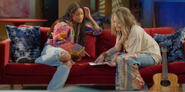 Willow Smith and Paris Jackson look at the same piece of paper while sitting on a red couch together.