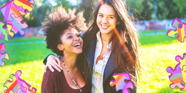 Two women with their arms around each other are standing in a sunny park. One woman has natural hair and a scoopneck shirt, the other is wearing a button-up and leather jacket with straight hair.
