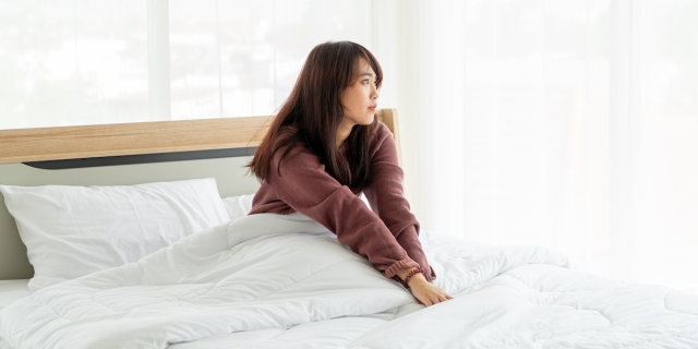 A person with long black hair wearing a sweatshirt sits in a white comforter on a bed, looking off into the distance