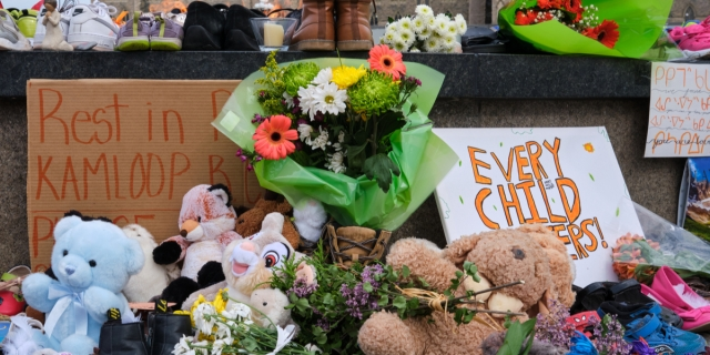 A memorial assembled for children found at Kamloops Residental School, featuring flowers, stuffed animals and children's toys, as well as signs that read REST IN PEACE KAMLOOPS and EVERY CHILD MATTERS