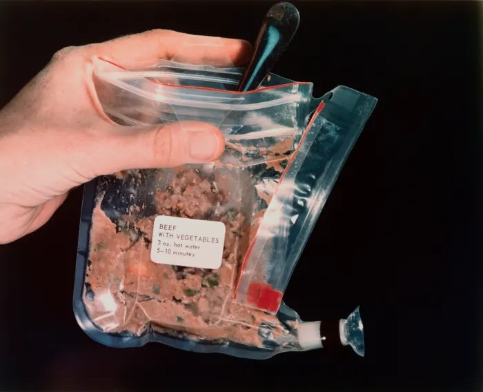 An open plastic package of dehydrated brown food with the label BEEF WITH VEGETABLES