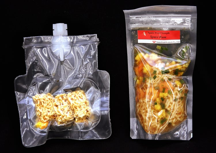 Vacuum packed plastic pouches of cooked noodles for astronauts labeled Space Ram