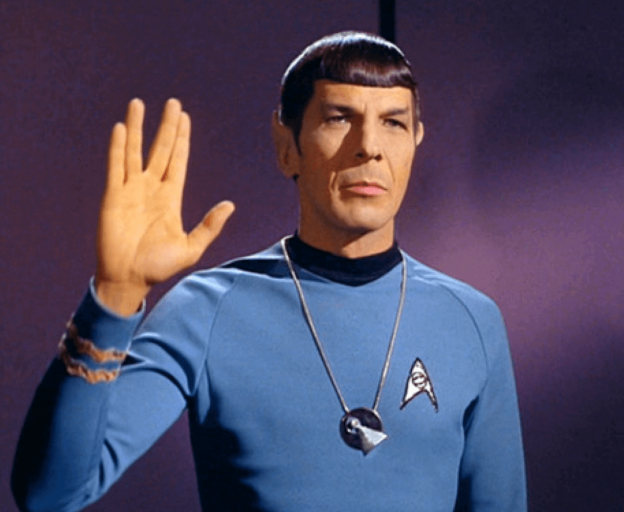Spock from Star Trek in his blue uniform making the classic Vulcan hand sign