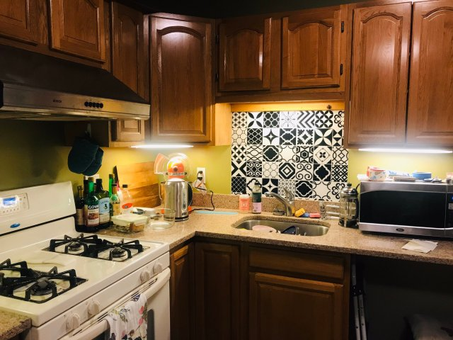 Kitchen with bright yellow walls, black and white tile mosaic, and colorful kitchen tools arranged on countertop