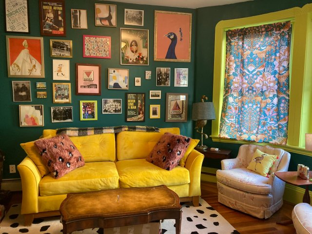 Living room with dark turquoise walls, chartreuse trim on the window frame, a bright yellow couch, a black and white dotted rug, rust-colored pillows, and a wide variety of framed prints of different sizes and colors