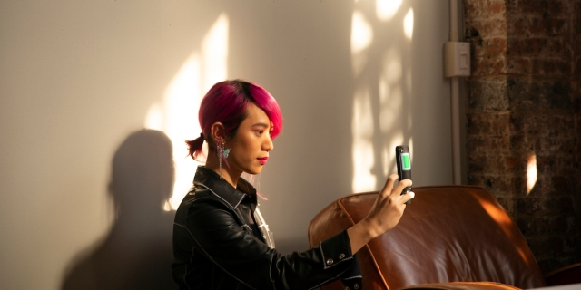 A person with pink hair in a short ponytail takes a selfie with their phone in a sunlit loft. Photo by Zackary Drucker as part of Broadly's Gender Spectrum Collection. Credit: The Gender Spectrum Collection. Made available to media outlets via Creative Commons.