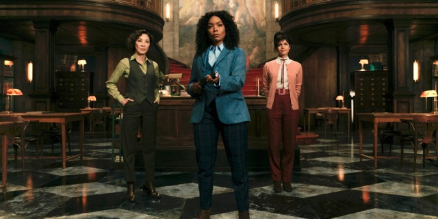 In this review for Gunpowder Milkshake, Angela Bassett has on a blue suit and holds a firearm, Michelle Yeoh and Carla Gugino are behind her.
