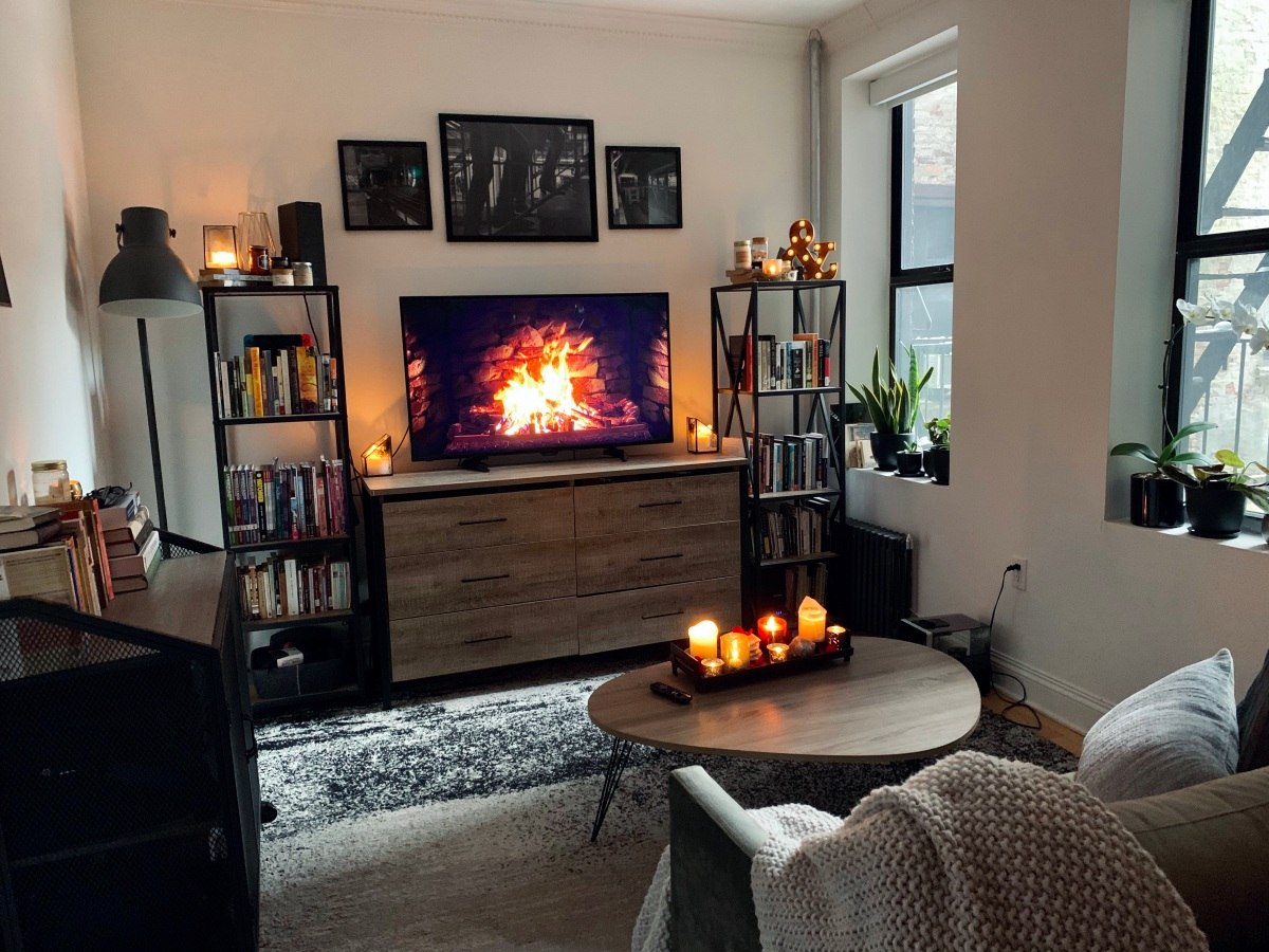 Living room with television playing fire video, bookcases covered in lit candles, and a coffee table in front of a sofa that also holds a tray of burning candles. Windows on the side have plants on the sills, a rug is on the floor, and the couch has a large throw blanket on one corner
