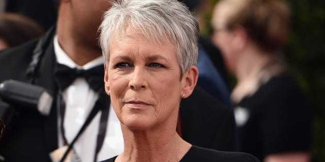 A silver haired Jamie Lee Curtis looks intensely into the camera with a black dress on.
