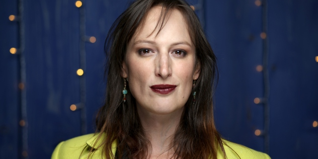 Jen Richards interview: Jen Richards in a chartreuse top and dark lipstick against a navy blue background