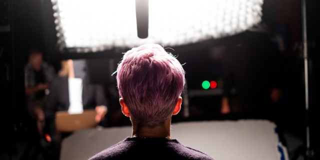 LFG Review: The back of Megan Rapinoe's head is backlight against a bright camera light with a microphone hanging in front of her.