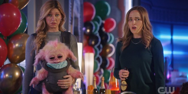 Legends of Tomorrow Episode 609: Avalance, Sara and Ava, at a birthday party looking surprised and holding a baby alien