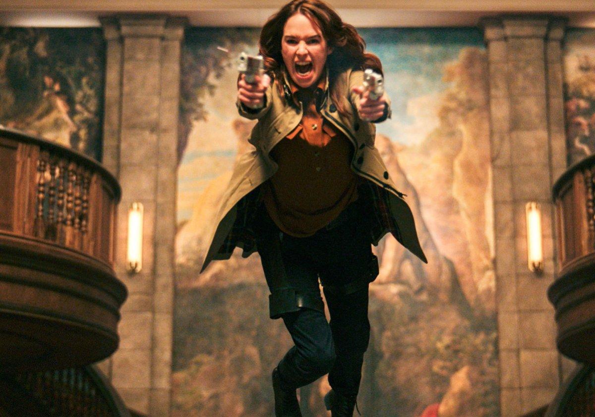 Lena Headey comes over a desk screaming with guns in both hands in Gunpowder Milkshake
