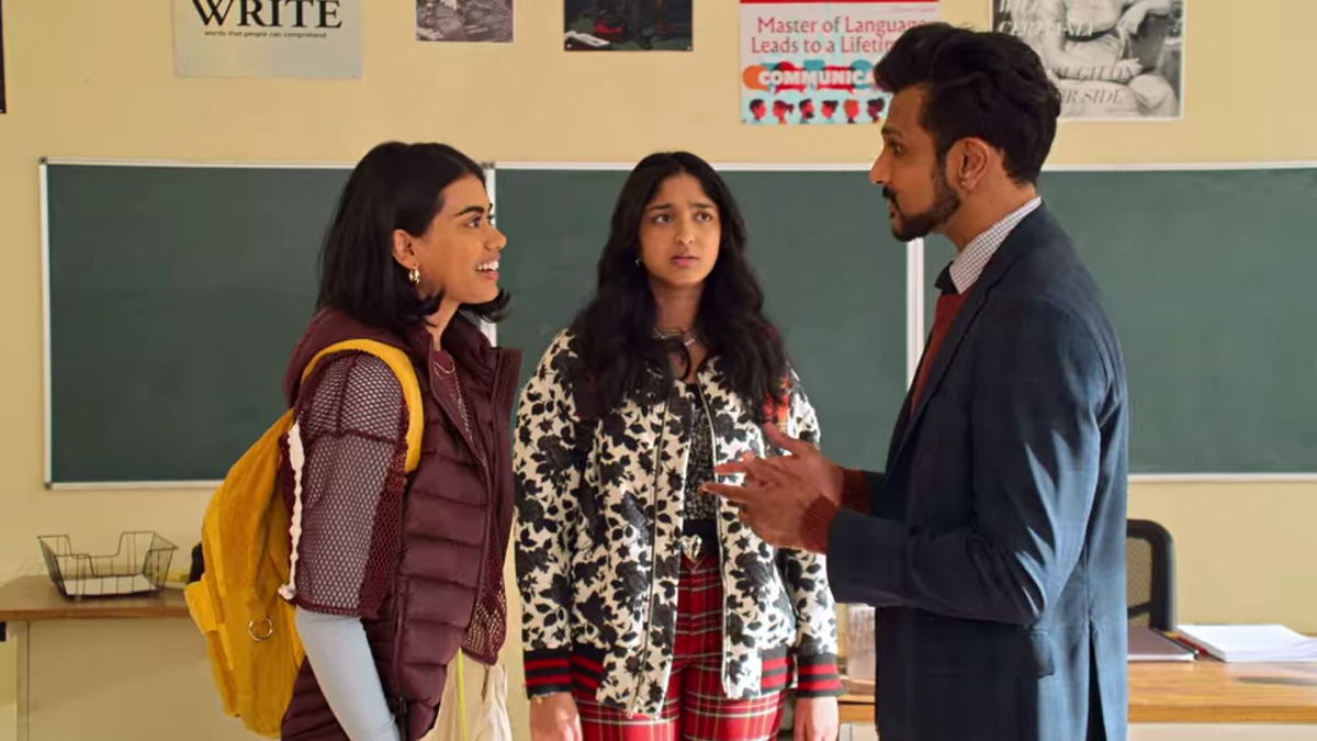 Aneesa smiles as she talks to Mr. Kulkarni in his classroom, one of the school's teachers who is also South Asian. Devi stands behind them, frowning with a look of betrayal on her face as she looks at Mr. Kulkarni.