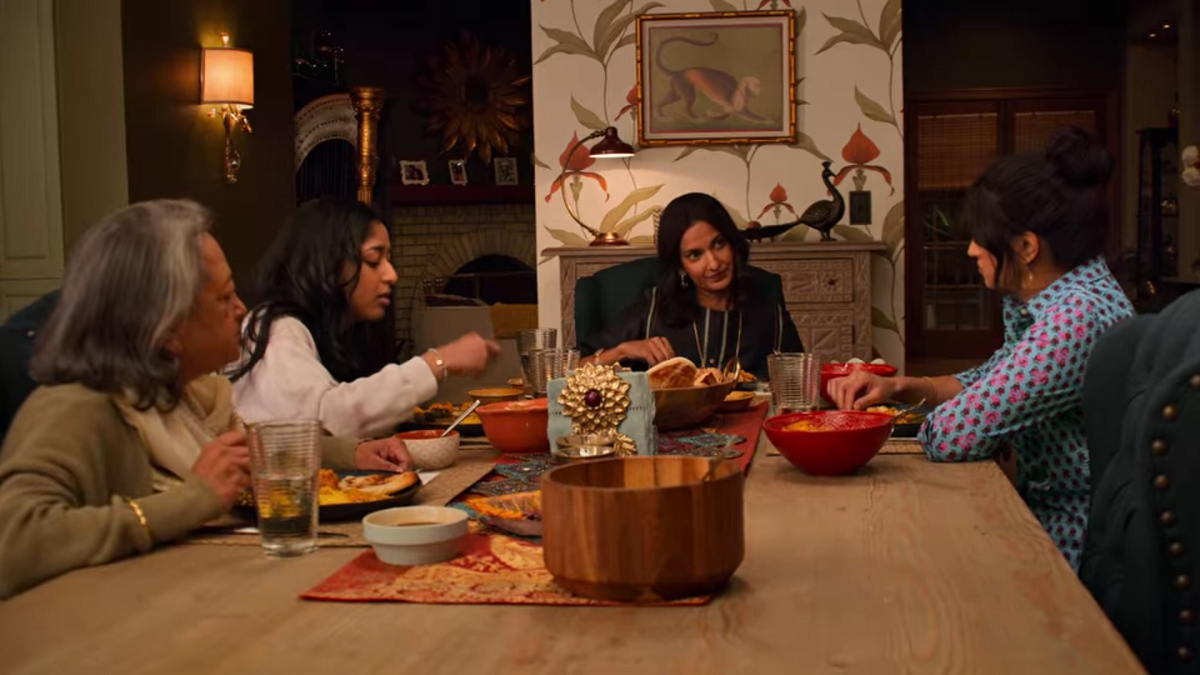 The Vishwakumar family sits around a table eating dinner. Nalini sits at the head of the table and is speaking with Kamala, to her left. Devi sits on Nalini's right and Nirmala is in the foreground of the image, next to Devi. The family is eating a traditional Indian meal prepared by Nirmala.