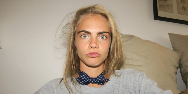 Cara Delevingne in a close up making silly faces with her eyebrows showing prominently