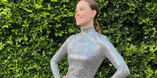 Evan Rachel Wood is in a sparkly silver gown in front of a green leafy wall, her hair is in a low slick ponytail.