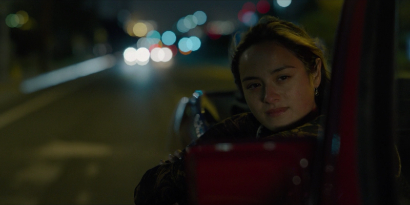 Riley sits in the passenger seat of Chester's car late at night with her arm and head hanging off the side