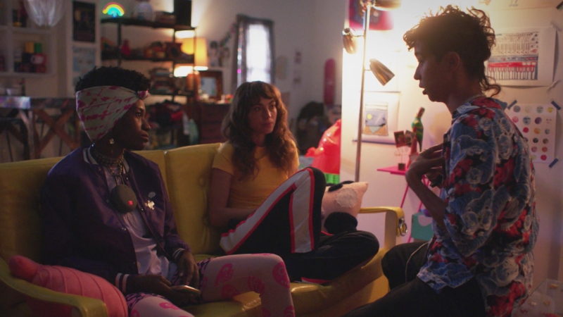 Victoria talks to Honeybear and Ash who are next to each other on a yellow couch