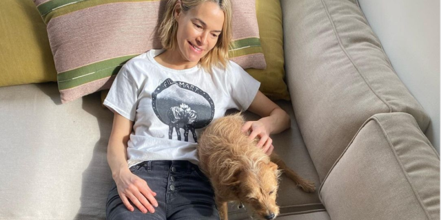 A cropped photo of Leisha Hailey gazing adoringly at a small dog while reclined on a sofa