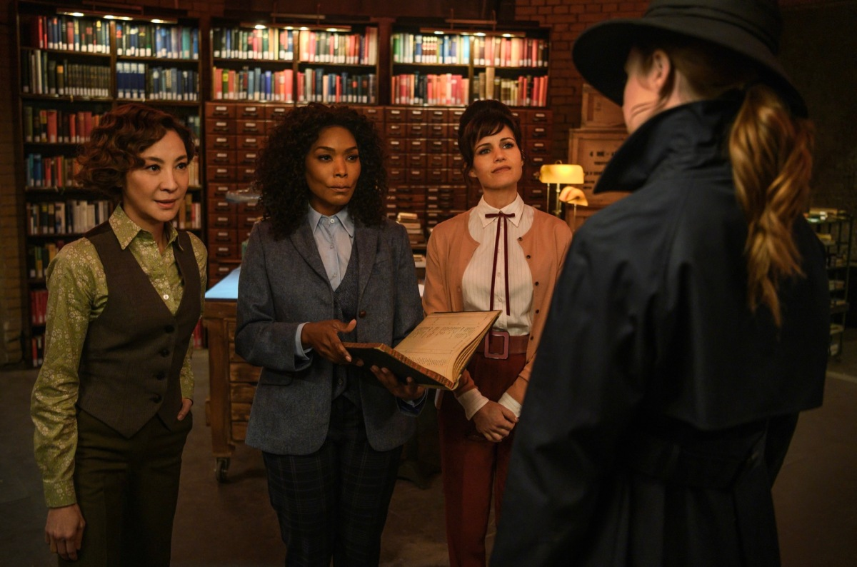 Michelle Yeoh, Angela Bassett, and Carla Gugino are the Librarians, dressed in suits that are green (Yeoh), blue (Bassett), and Pink (Gugino)