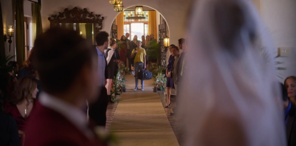 Finley standing at the other side of the wedding room with her duffel bag
