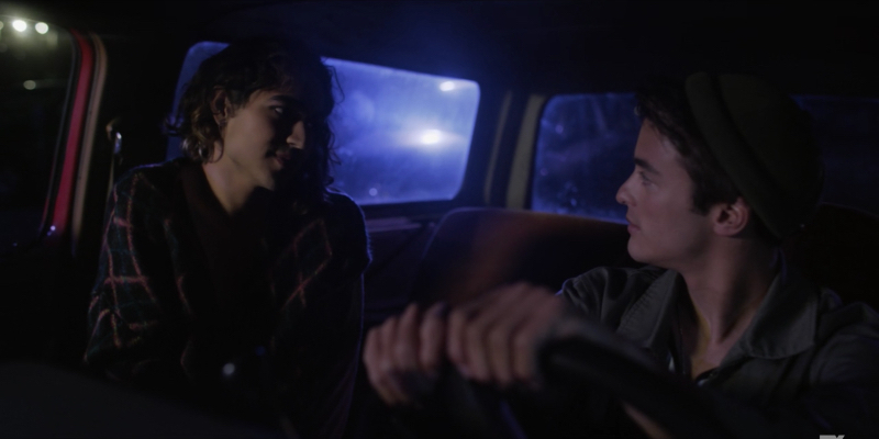 Dee played by Ben J. Pierce looks longingly at a cis boy next to them in a car.