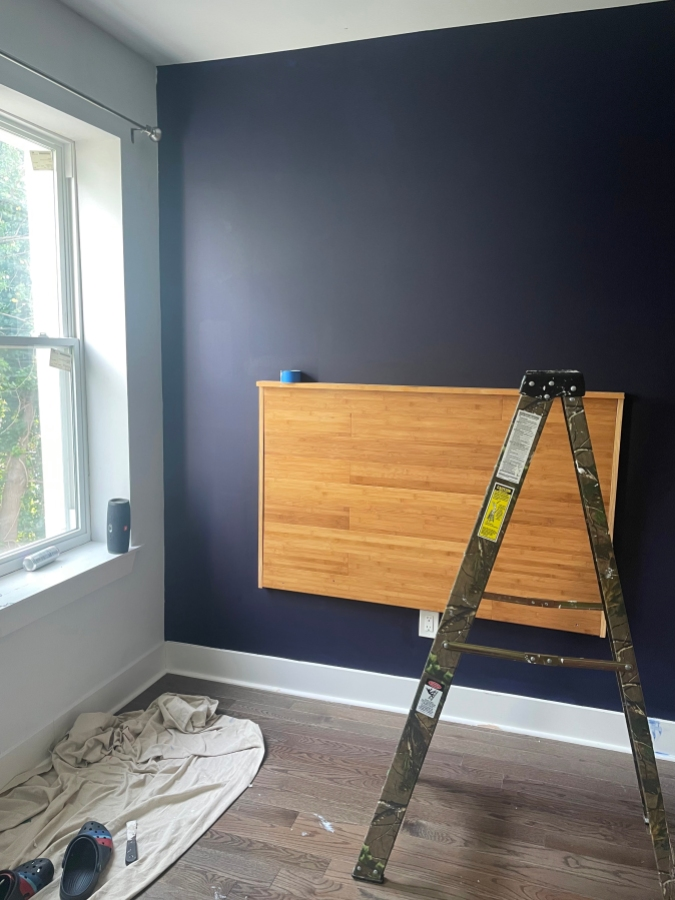 A dark purple wall with a wooden headboard mounted on the wall, a ladder and a pair of Crocs in the foreground