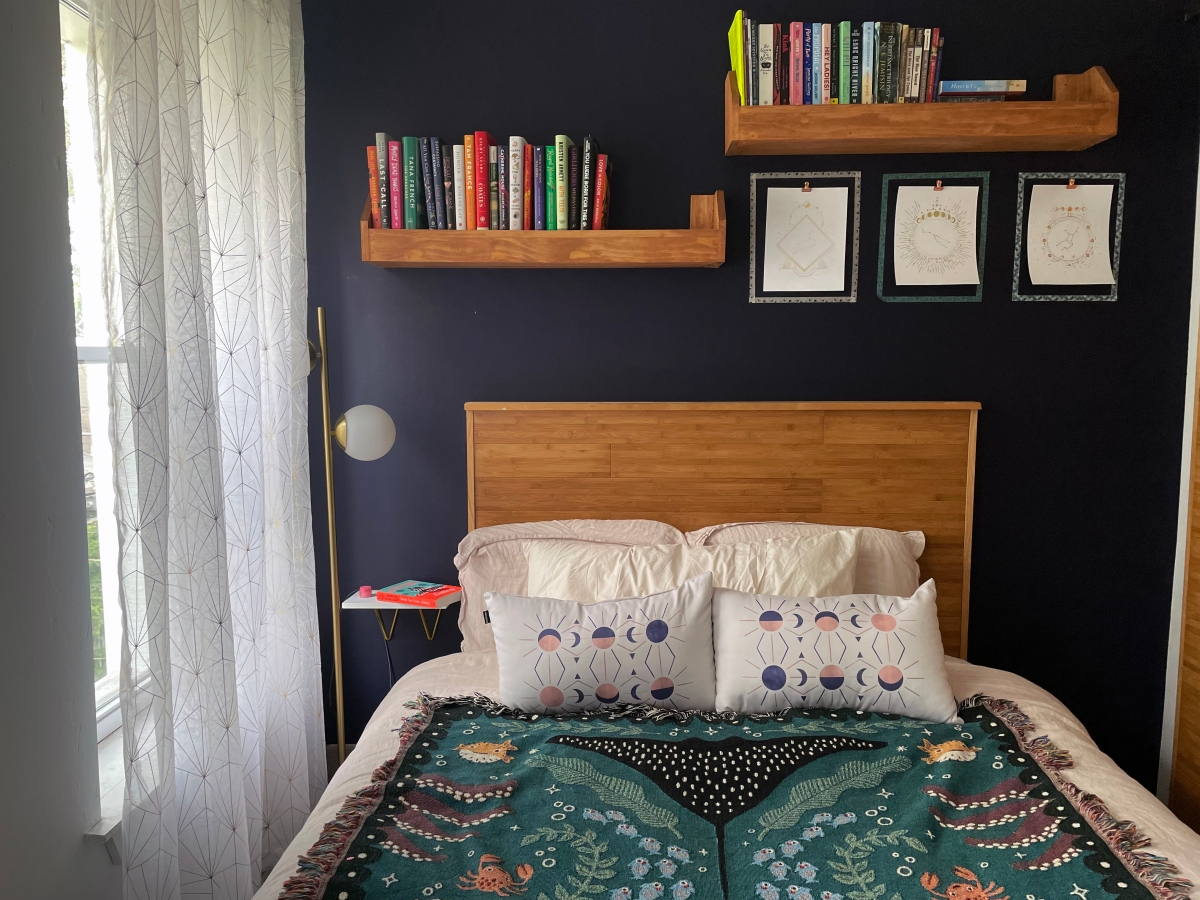 a bed with a mermaid throw on top of it, bookshelves and a gold lamp