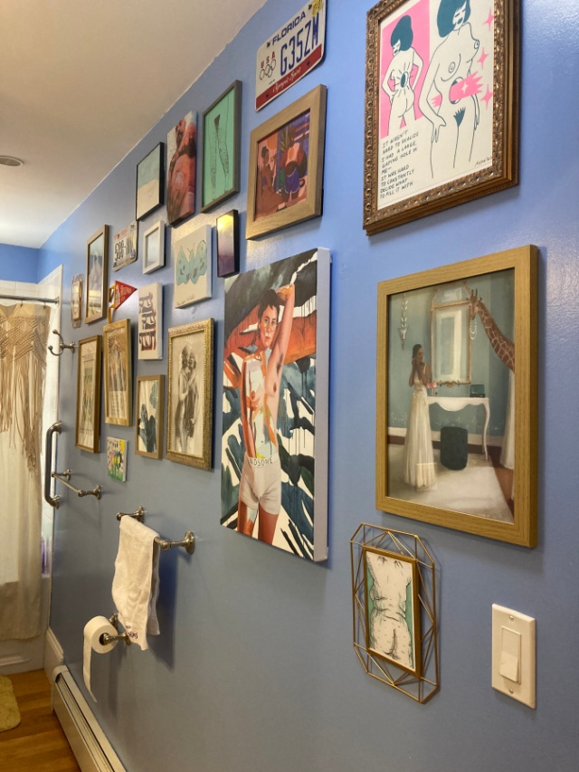 Powder blue bathroom wall covered in a variety of paintings and prints, including the figure with their hand in boxer shorts reading HANDSOME on the waistband