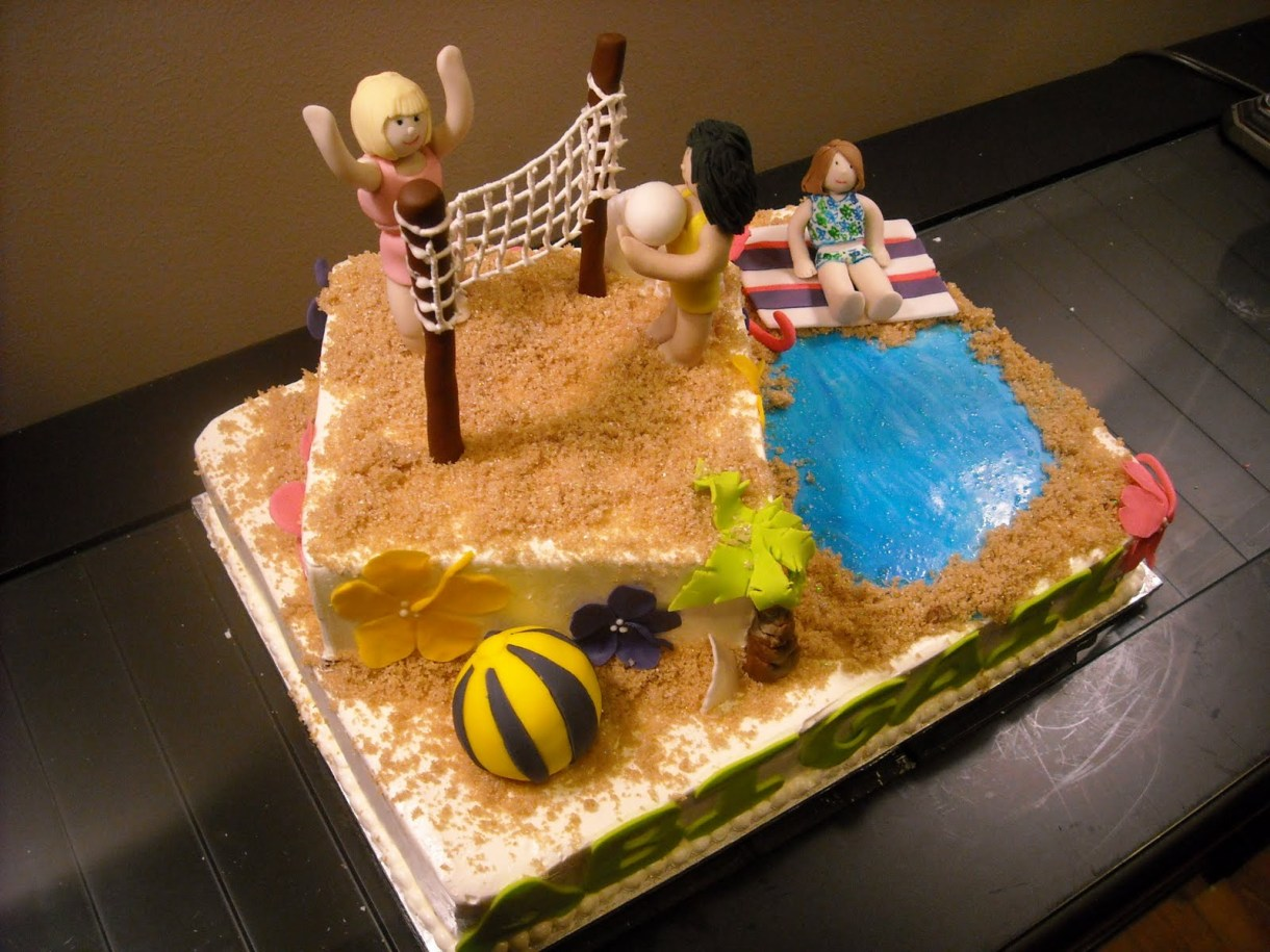 a cake decorated to look like a beach with people playing volleyball