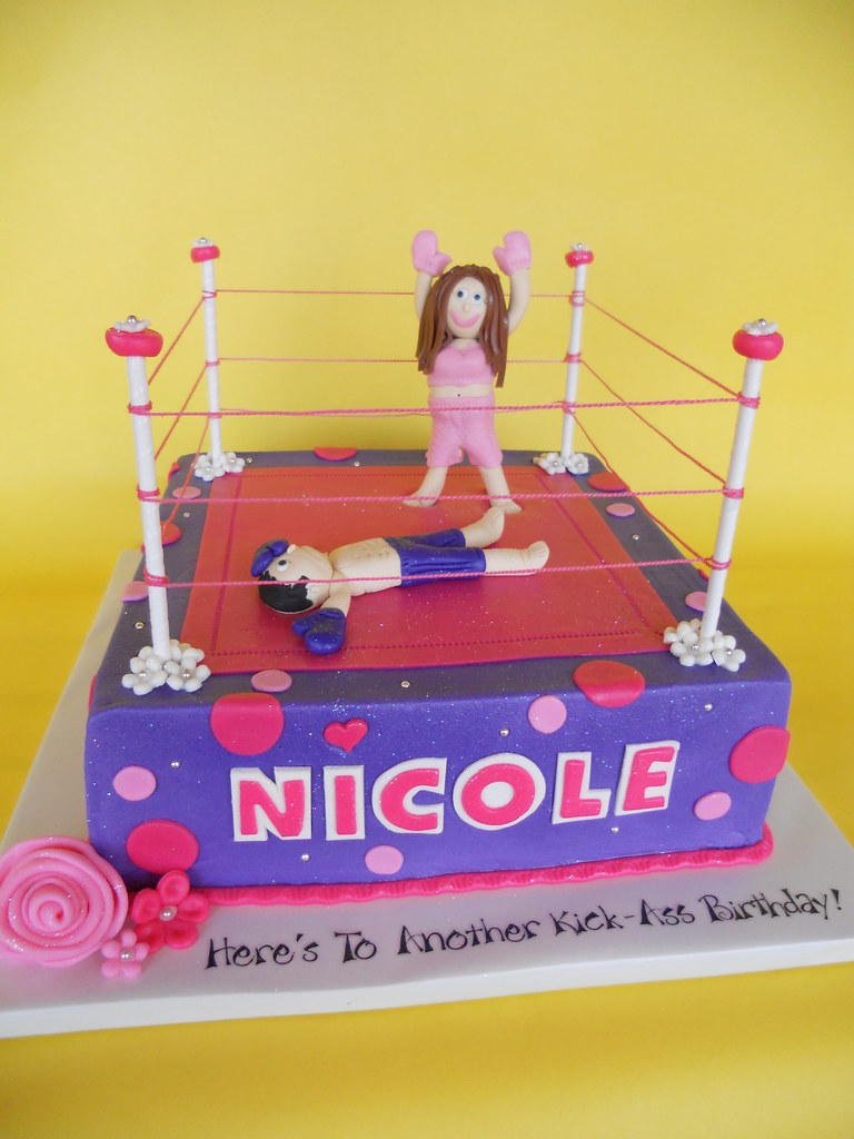 a cake that says nicole with a triumphant woman in a boxing ring having knocked out her opponent