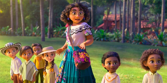 A screenshot of Disney's Ecnanto, with Stephanie Beatriz's Maribel in a white shirt and teal skirt in the grass of an enchanted village surrounded by little kids