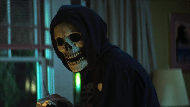 A masked skeleton guy in a black hoodie