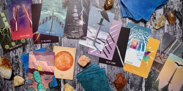 A scattered pile of beautiful brightly colored tarot cards and crystals across a wooden surface.