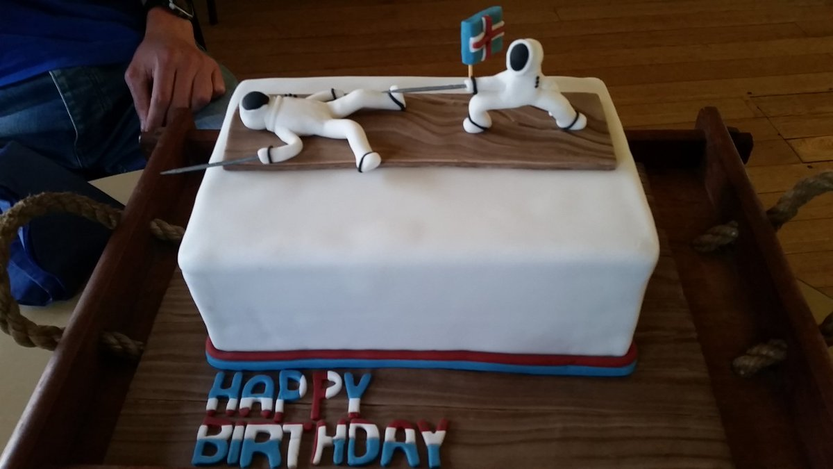 a cake decorated with a fencer knocking out another fencer